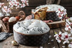Free Glazed Easter Cake Or Bread Kulich Decorated With Candy On Rustic Wooden Table With Colored Easter Eggs In Basket And Spring Stock Photography - 179040712