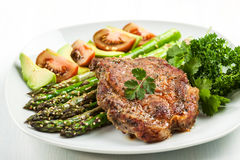 Glazed green asparagus with grilled pork chop Royalty Free Stock Photo