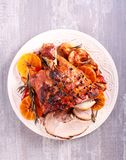 Glazed ham with apples and oranges. On plate royalty free stock image