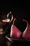 Glazed pears steeped in red wine. Glazed fresh whole pears steeped in red wine served for a speciality dessert with a silver sauce boat alongside in a dark Stock Photos