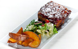 Glazed Pork Ribs with salad and baked potatoes. Juicy honey glazed pork ribs with side salad and baked potatoes Royalty Free Stock Image