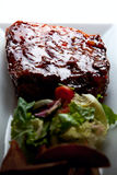 Glazed Pork Ribs with salad and baked potatoes. Juicy honey glazed pork ribs with side salad and baked potatoes Royalty Free Stock Photos