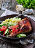 Glazed roasted chicken leg with mashed potatoes and vegetable salad on a wooden background Royalty Free Stock Images