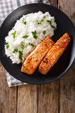 Glazed salmon fillet with rice garnish close-up. Vertical top vi Stock Photography