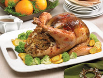 Glazed turkey with mushroom stuffing. Served with green cauliflower, yellow zucchini and oranges in background Royalty Free Stock Images