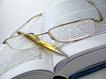 Glazen & pen op boek 2 stock foto