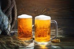 Glazen bier en droge vissen op een houten lijst stock foto's