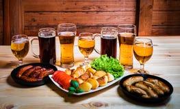 Glazen bier en geroosterde worsten op houten lijst Stock Afbeeldingen