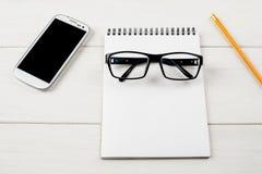 Glazen, blocnote, potlood en mobiel apparaat op een witte houten lijst stock foto