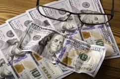 Glazen bovenop de rekeningen van $ 100 en de verfrommelde rekening van $ 100 Stock Afbeelding