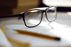 Glazen die in de werkplaats, onder een notitieboekje, potlood en andere punten liggen royalty-vrije stock afbeeldingen