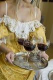 Glazen die met rode wijn op een mooi dienblad worden gevuld. royalty-vrije stock afbeeldingen