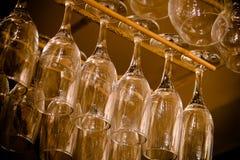 Glazen die ondersteboven in een bar hangen Stock Afbeeldingen