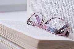 Glazen die op een boek liggen Stock Foto's
