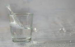 Glazen die water en met plonsen en dalingen vallen springen stock afbeeldingen