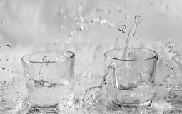 Glazen die water en met plonsen en dalingen vallen springen royalty-vrije stock afbeeldingen