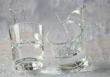 Glazen die water en met plonsen en dalingen vallen springen stock foto