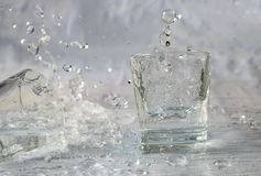 Glazen die water en met plonsen en dalingen vallen springen royalty-vrije stock fotografie