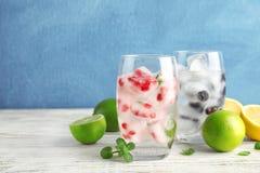 Glazen dranken met fruitijsblokjes op lijst tegen kleurenachtergrond stock afbeelding