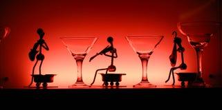 Glazen en beeldjes in rood licht Stock Fotografie