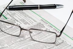 Glazen en een pen op een voorraadsectie van het redactie slechts gebruik van Wall Street Journalfor royalty-vrije stock afbeeldingen