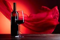 Glazen en fles redewijn op een rode achtergrond Rood zuiver F Royalty-vrije Stock Foto's