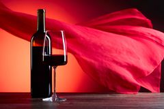 Glazen en fles redewijn op een rode achtergrond Rood zuiver F Stock Foto