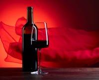 Glazen en fles redewijn op een rode achtergrond Rood zuiver F Royalty-vrije Stock Fotografie