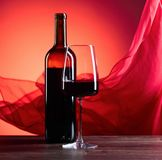 Glazen en fles redewijn op een rode achtergrond Rood zuiver F Royalty-vrije Stock Foto