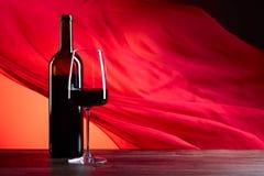 Glazen en fles redewijn op een rode achtergrond Rood zuiver F Stock Afbeeldingen