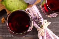 Glazen en fles rode wijn met druif, lavendel en pestokaas op hakbord stock fotografie