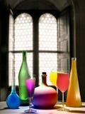 Glazen en flessen met kleurrijke vloeistoffen Stock Fotografie
