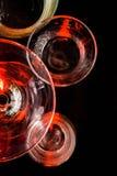 Glazen en glazen door gekleurd licht op een zwarte achtergrond worden benadrukt die Royalty-vrije Stock Foto
