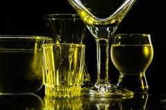 Glazen en glazen door gekleurd licht op een zwarte achtergrond worden benadrukt die Stock Afbeelding