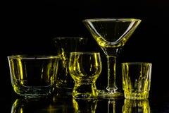 Glazen en glazen door gekleurd licht op een zwarte achtergrond worden benadrukt die Royalty-vrije Stock Afbeeldingen