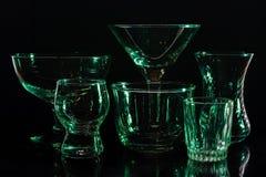 Glazen en glazen door gekleurd licht op een zwarte achtergrond worden benadrukt die Stock Afbeeldingen