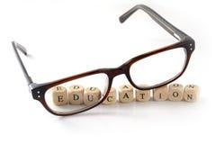 Glazen en onderwijsbericht dat in houten geïsoleerde blokken wordt geschreven, Stock Fotografie