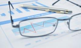 Glazen en pen op financiële grafiek en grafiek, succesconcept stock fotografie