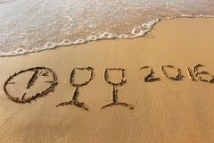 Glazen, klok die, het jaar van 2016 op zandige strandoverzees die wordt geschreven Stock Afbeeldingen