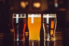 Glazen licht en donker bier op een barachtergrond Stock Foto