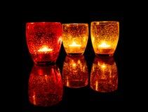 Glazen met aangestoken kaarsen op een zwarte lijst Royalty-vrije Stock Foto