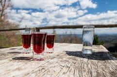 Glazen met alcoholische drank op houten lijst met toneelmening Stock Afbeeldingen