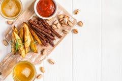 Glazen met bier, Aardappelplakken en saus, worsten en pistaches Snackbarmenu Royalty-vrije Stock Afbeelding