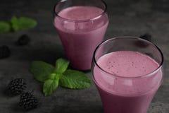 Glazen met braambessenyoghurt smoothies op grijze lijst royalty-vrije stock afbeeldingen