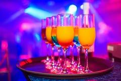 Glazen met diverse alcoholische dranken en cocktails met gekleurde vage achtergrond op vieringspartij in nachtclub Stock Afbeeldingen