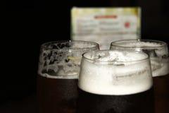 Glazen met donker bier op de bar stock foto's