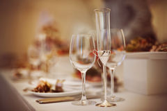Glazen met dranken en schotels worden geplaatst die Stock Foto