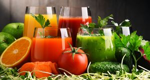 Glazen met verse organische groente en vruchtensappen stock foto