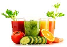 Glazen met verse organische groente en vruchtensappen op wit Stock Foto's