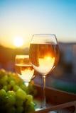 Glazen met witte wijn bij zonsondergang, met de bezinning van de huizen stock fotografie